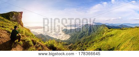 Panorama beautiful landscape nature Male tourist are watching the sunrise on peak mountain with sun cloud fog and bright sky in winter at Phu Chi Fa Forest Park famous attraction of Chiang Rai Province Thailand