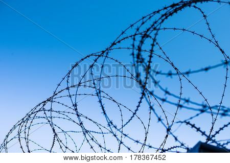 Top of fortress concrete security wall topped with barbed wire against blue sky background - view from prison and freedom concept