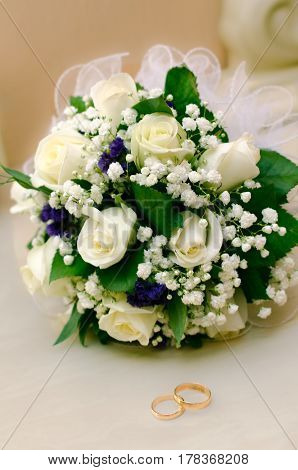 wedding rings and Wedding bouquet white roses.