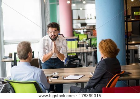 Young bearded man asking to give him job position in company. Handsome man communicating with business representatives of company.