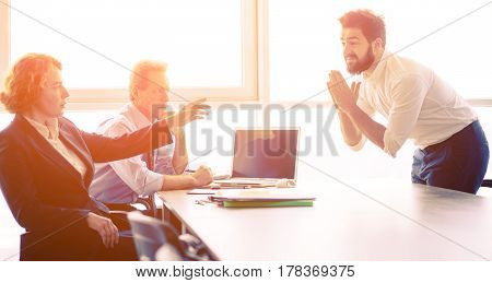 Toned of young bearded man came from India asking employees to offer him job position in company. Handsome man clasped his hands. Employees listening to him.