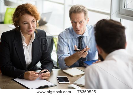 Happy HR specialists of company taking interview. People communicating with young man and asking him to tell about his previous experience.