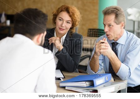 Business representatives communicating with young man and asking him to tell about his previous experience. Happy HR specialists of company taking interview.