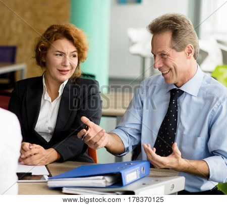 Business negotiations concept. Happy business partners smiling and communicating with young man concerning business projects, strategies, etc.