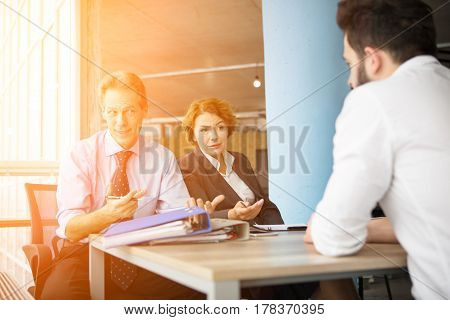 Executive people taking interview in office by asking young man several provisions from his CV. Experience concept.