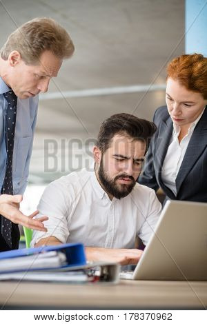 Mobbing, stress, work, scandal concepts. Angry bosses man and woman screaming and shouting at their worker while he is working on laptop computer.