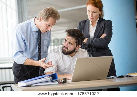 Mobbing, stress, work, scandal concepts. Angry boss man explaining his worker what to do first while woman posing with crossed hands and listening to him.