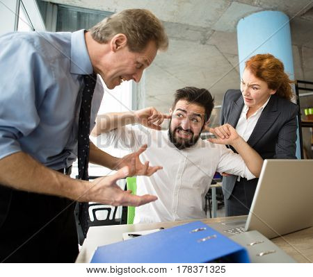 Mobbing, stress, work, scandal concepts. Angry bosses man and woman screaming, shouting and yelling at their worker. Handsome man having stress and closing with ears.