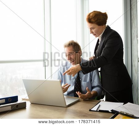 Mobbing, stress, work, scandal concepts. Red haired business lady explaining her subordinate what to do first while he is sitting in front of laptop computer and screaming.