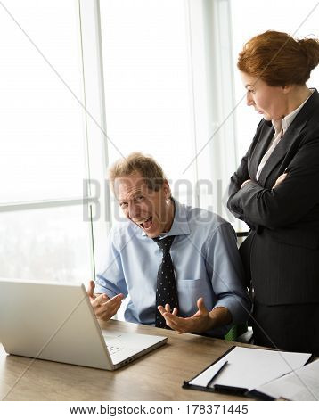 Beautiful red haired business lady explaining her subordinate what to do first. Businessman sitting in front of laptop computer and screaming. Mobbing, stress, work, scandal concepts.