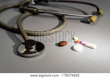 Stethoscope close-up. Next to tablets and capsules the diagnosis result is