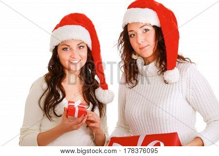 Two happy women in santa hats with gift boxes standing on white background.