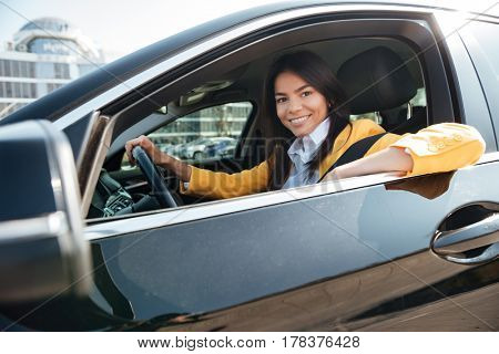 Portrait of a pretty business woman sitting in her new car and looking at camera