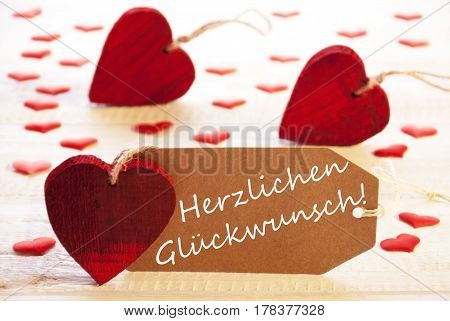 Label With German Text Herzlichen Glueckwunsch Means Congratulations. Many Red Hearts on Wooden Rustic Or Vintage Background.