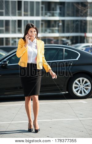 Full length portrait of a smiling attractive business woman talking on mobile phone while walking outdoors