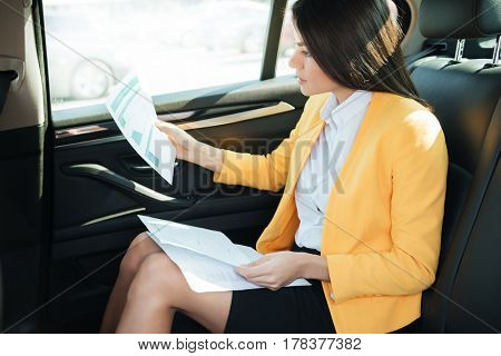 Side view of a concentrated businesss woman analyzing documents while sitting on the back seat of a car