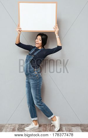 Photo of pregnant happy woman standing and posing while showing copyspace blank over grey background. Looking at camera.