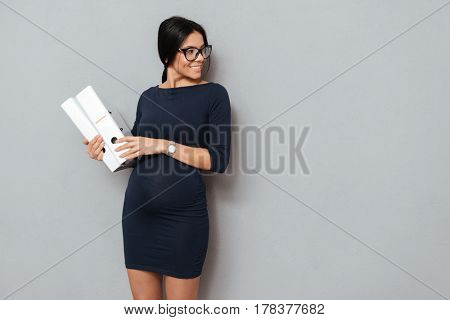 Image of happy pregnant business woman wearing glasses holding folders standing over grey background. Looking away.