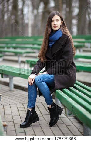 Young Beautiful Girl In A Black Coat Blue Scarf Glasses Sitting On Bench In City Park. An Elegant Br