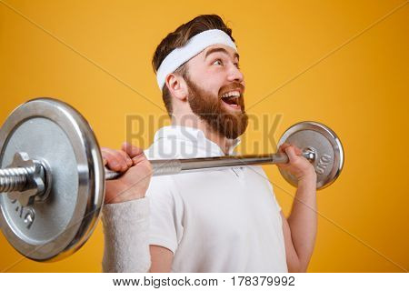 Close up portrait of an excited bearded fitness man workout with barbell isolated on a white background