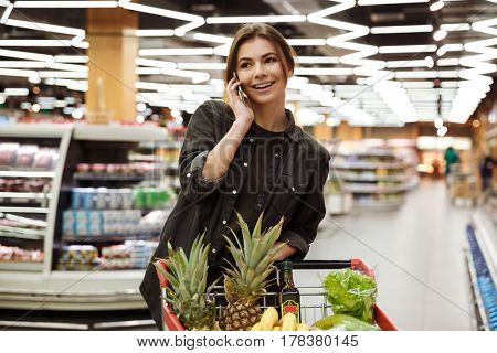 Image of young happy woman in supermarket with shopping trolley choosing products and talking by phone. Looking aside.