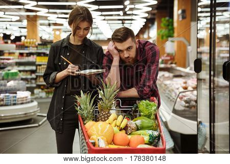 Photo of young loving couple in supermarket with shopping trolley choosing products. Tired man looking at camera.