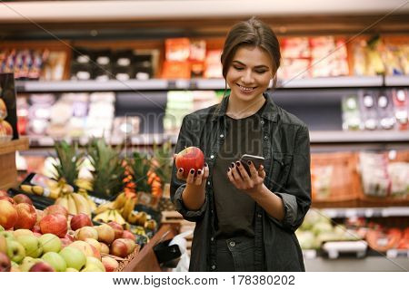 Image of happy young lady standing in supermarket holding apple and chatting by phone. Looking at phone.