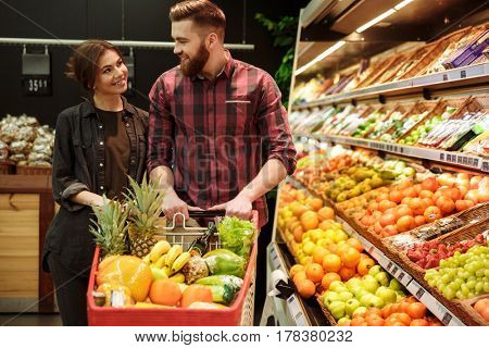 Photo of young happy loving couple in supermarket with shopping trolley choosing fruits. Looking aside.