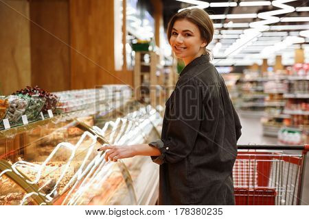Picture of happy lady standing in supermarket choosing pastries. Looking at camera.