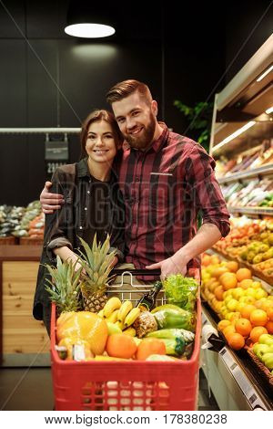 Picture of young cheerful loving couple in supermarket with shopping trolley choosing fruits. Looking at camera.