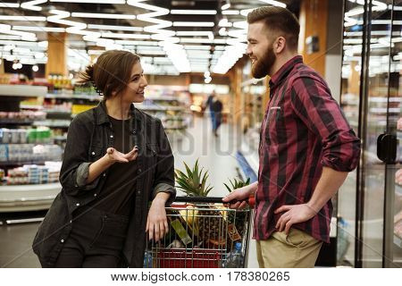 Picture of young happy loving couple talking in supermarket with shopping trolley choosing products. Looking at each other.