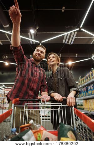 Picture of cheerful young loving couple in supermarket with shopping trolley choosing products. Looking aside and pointing.