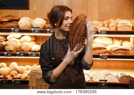 Photo of young happy woman in supermarket choosing and smells bread.