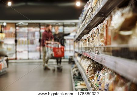 Image of concentrated young loving couple in supermarket choosing products. Looking aside. Focus on products.