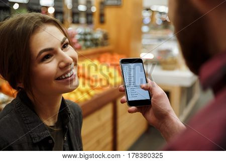 Image of young loving couple standing in supermarket holding list of purchases in phone. Focus on woman.