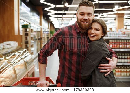 Photo of cheerful young loving couple standing in supermarket and hugging. Looking at camera.