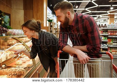 Photo of concentrated young loving couple standing in supermarket choosing pastries. Looking aside.