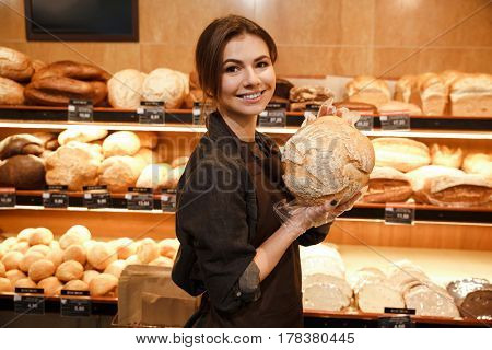 Photo of young cheerful woman in supermarket choosing pastries. Looking at camera.