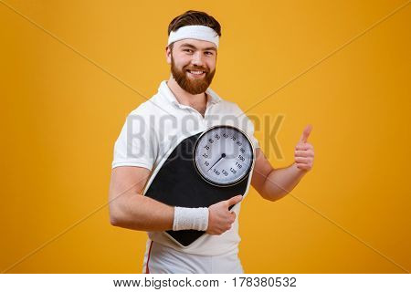 Portrait of a happy smiling bearded fitness man holding weight scales and showing thumbs up isolated on orange background