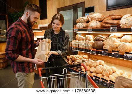 Image of young smiling loving couple in supermarket choosing pastries. Looking aside.