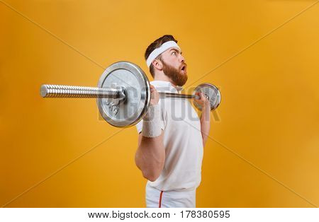 Image of concentrated young sportsman make sport exercises with barbell isolated over yellow background. Looking aside.