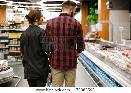 Back view picture of young loving couple standing in supermarket choosing products.