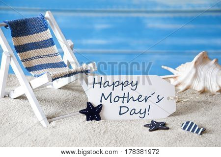 Summer Label With English Text Happy Mothers Day. Blue Wooden Background. Card With Holiday Greetings. Beach Vacation Symbolized By Sand, Deck Chair And Shell.
