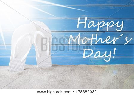 English Text Happy Mothers Day. Sunny Summer Greeting Card With Sand And Flip Flops. Blue Vintage And Shabby Chic Wooden Background.