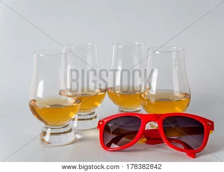 Delicious Single Malt Whiskey Glass With Sunglasses On A White Background