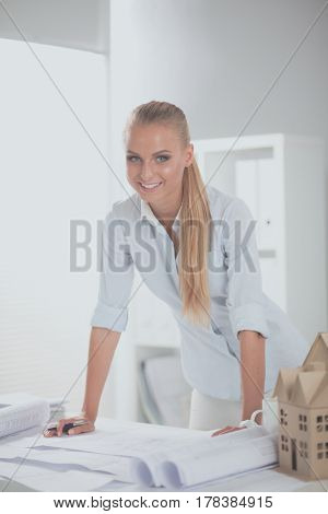 Portrait of female architect with blueprints at desk in office