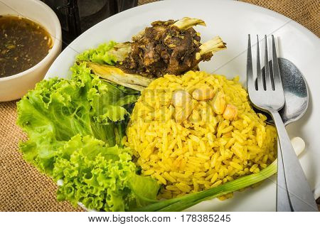 Mutton Byriani - Lamb and rice cooked with spices. Served with raita. Traditional South Asian Cuisine.