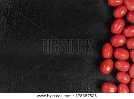 Overhead view of fresh cherry tomatoes on black slate with available copy space on left side