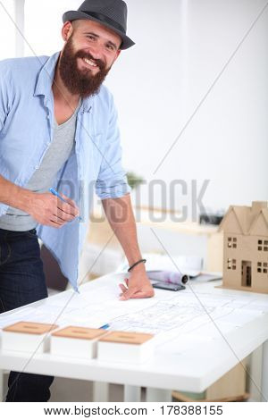 Portrait of male designer in hat with blueprints at desk