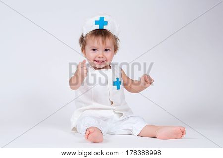 Cheerful laughing baby girl playing as a doctor